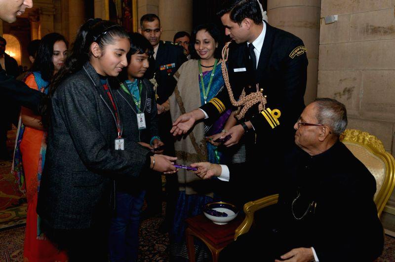 A child presents a chocolate to President Pranab Mukherjee at Rashtrapati Bhavan in New Delhi, on Jan 1, 2015. - Pranab Mukherjee