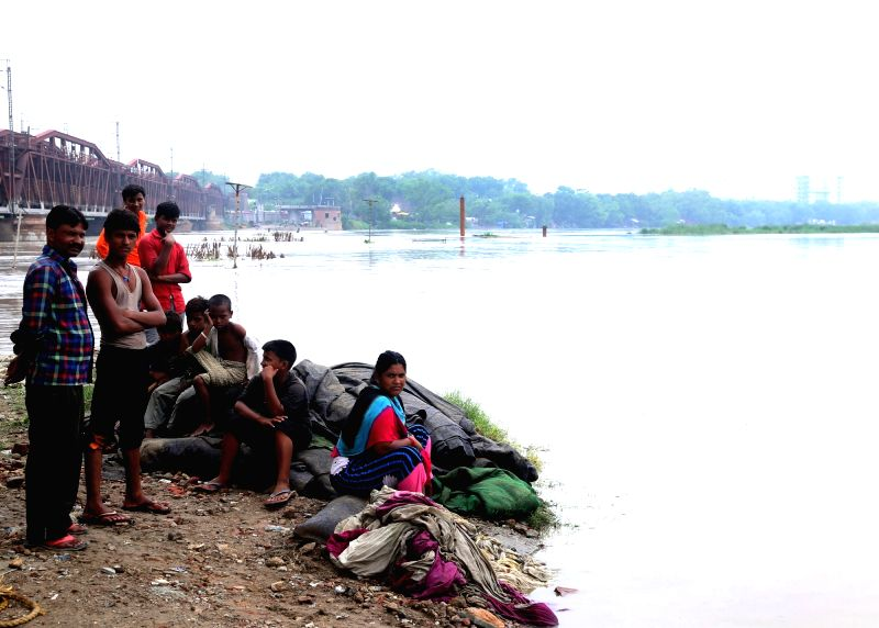 : New Delhi: A family sits with their belongings at the banks of river Yamuna as evacuation drive is underway after water released from Haryana's Hathnikund added to the continued rains that ...