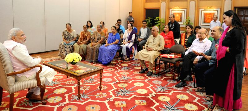A group of Gujarati families from Singapore, who are currently on a visit to India calls on the Prime Minister Narendra Modi, in New Delhi on March 30, 2015. - Narendra Modi