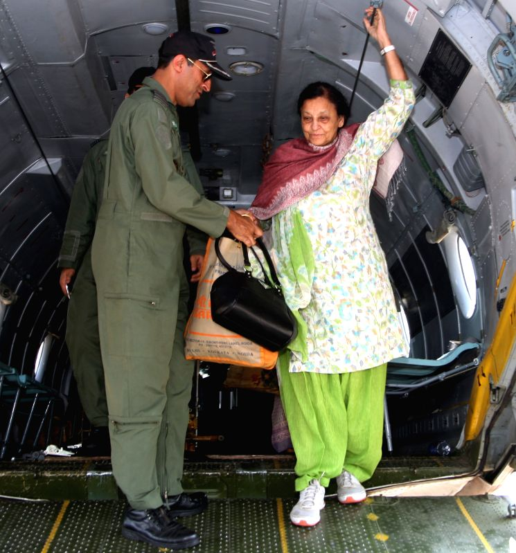 A lady who was rescued from earth-quake hit Nepal de-boards an IAF Transport Aircraft at Palam Airport on April 28, 2015.