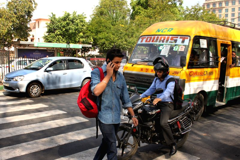 A man risks his life as he crosses road while speaking over his moblie phone in New Delhi, on April 10, 2015.
