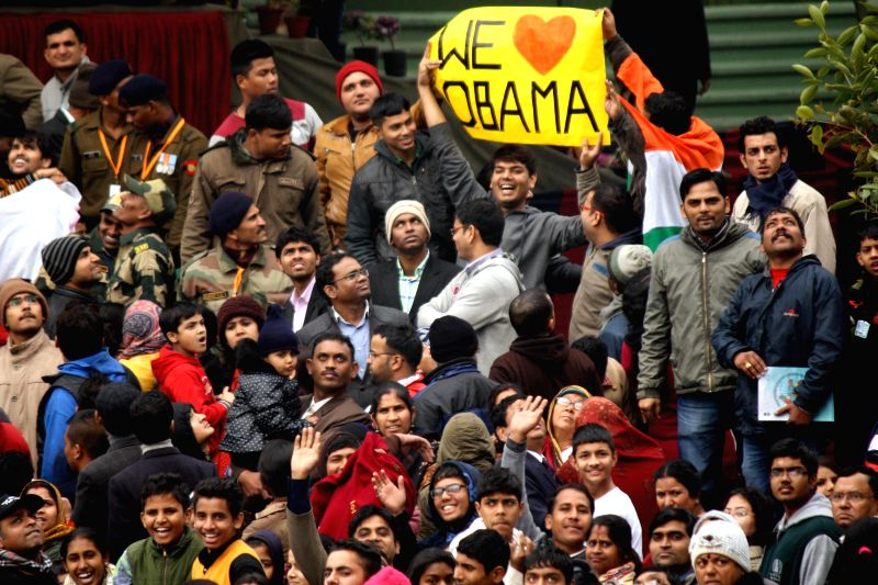 """A man standing among the spectators holds a placard reading """"We love Obama"""" during Republic Day celebrations in New Delhi, on Jan 26, 2015."""