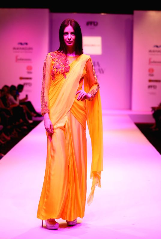 A model walks the ramp for fashion designer Jenjum Gadi during the fourth season of the India Runway Week, Spring Summer Collection - 2015 in New Delhi, on April 10, 2015.