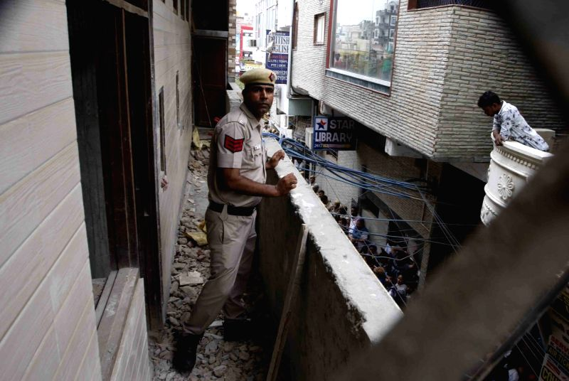 New Delhi: A police personnel carries out investigation at the site where 11 members of a family were found dead -- some blindfolded and hanging from an iron grill ceiling -- at their home, in New Delhi on July 1, 2018. According to Joint Commissione