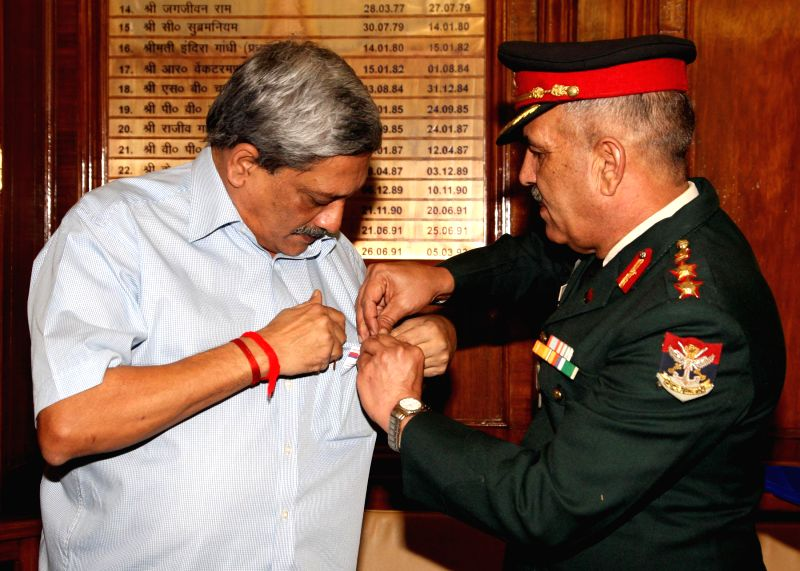 "A Service officer from Kendriya Sainik Board pins a lapel on the Union Minister for Defence, Manohar Parrikar on the eve of ""Armed Forces Flag Day"", in New Delhi on Dec 5, 2014."