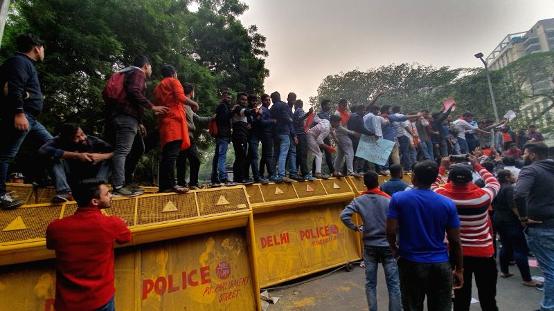 New Delhi: ABVP students climb up barricading as Delhi police halts its protest march towards the Ministry of Human Resource Development near Parliament street police station, called against the proposed hostel fee hike in JNU; in New Delhi on Nov 21