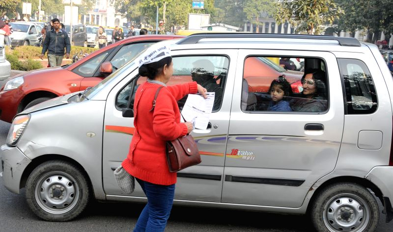 An Aam Aadmi Party (AAP) volunteer distributes pamphlets during an election campaign ahead of Delhi Assembly elections expected to be held in February 2015, in New Delhi.