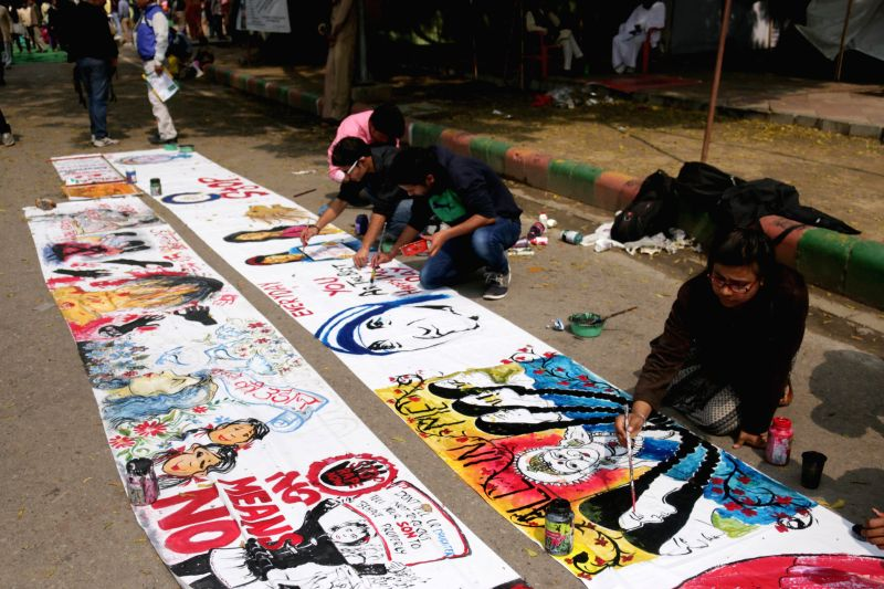 Artists busy painting during a programme organised to observe International Women's Day at Jantar Mantar in New Delhi, on March 8, 2015.