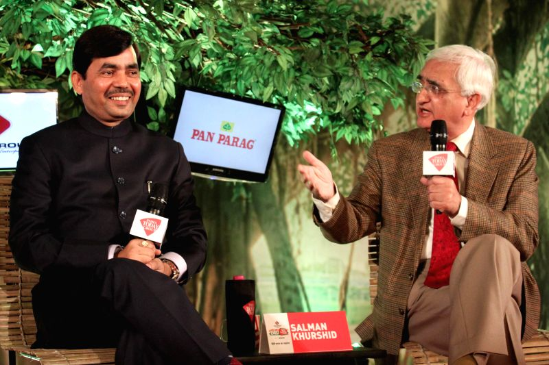 BJP leader Syed Shahnawaz Hussain with Congress leader Salman Khurshid during a programme organised by Aaj Tak news channel in New Delhi, on Dec 13, 2014.