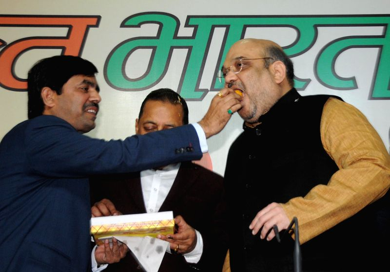 BJP spokesperson Syed Shahnawaz Hussain greets BJP chief Amit Shah during a press conference regarding party's performance in the recently held Jharkhand and Jammu and Kashmir polls at ...