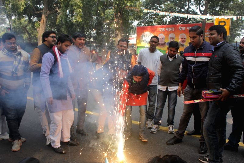 BJP workers celebrate party's performance in Jharkhand and Jammu and Kashmir Assembly polls in New Delhi on Dec 23, 2014. The party has won four seats and is leading in 33 seats in ...