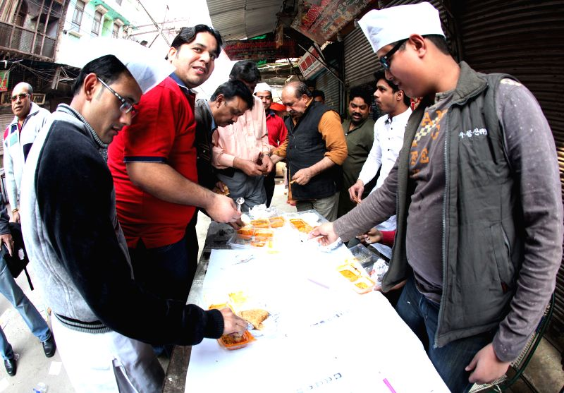Booth workers have snacks during Delhi Assembly Polls in New Delhi, on Feb 7, 2015.