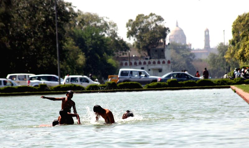 Children enjoy themselves near India Gate as the days get warmer in New Delhi, on March 18, 2015.