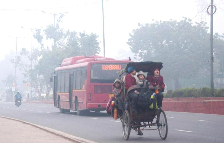 Children head towards school on a chilly foggy morning in New Delhi.