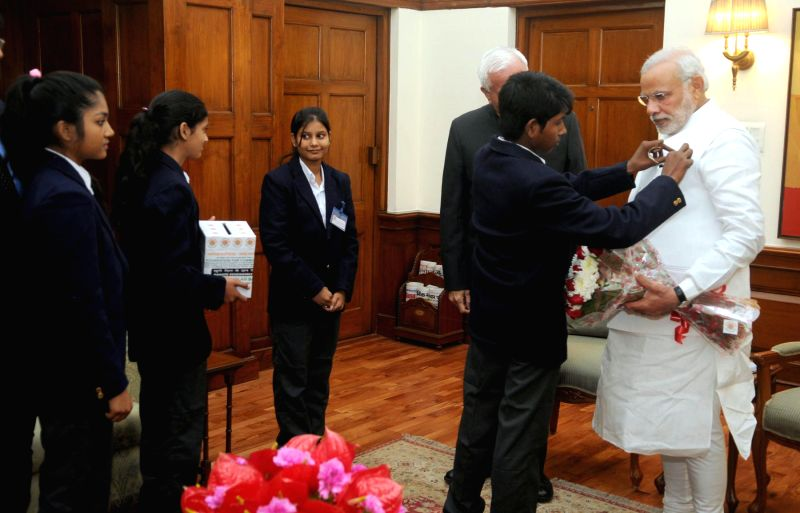 Children supported by National Foundation for Communal Harmony pinning a flag on the Prime Minister Narendra Modi, in New Delhi on Nov 24, 2014.