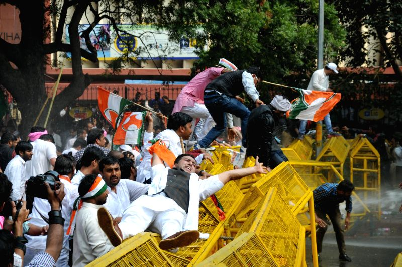 Congress workers break barricades during a demonstration against land acquisition bill at Jantar Mantar in New Delhi, on March 16, 2015.