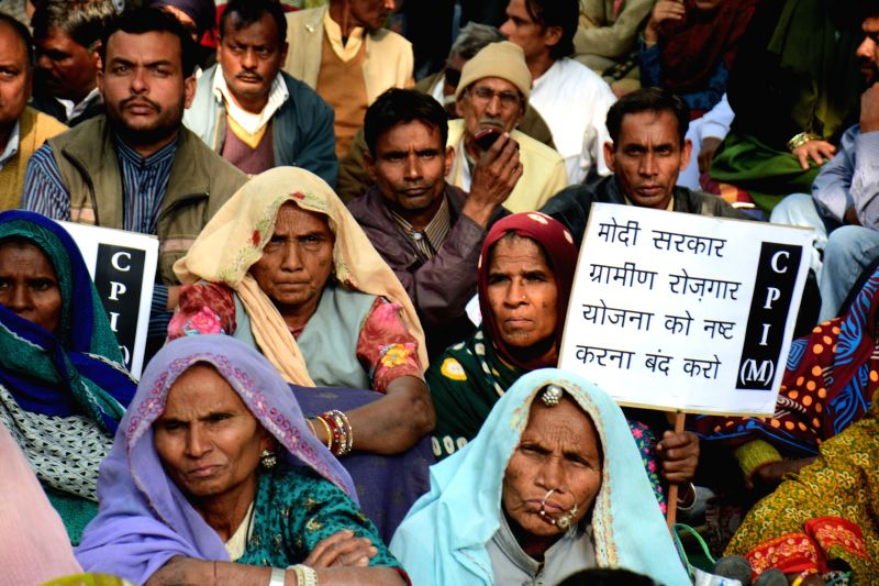 CPI(M) workers stage a demonstration to protest against the curtailment of MGNREGA rural job scheme by the central government in New Delhi, on Nov 26, 2014.