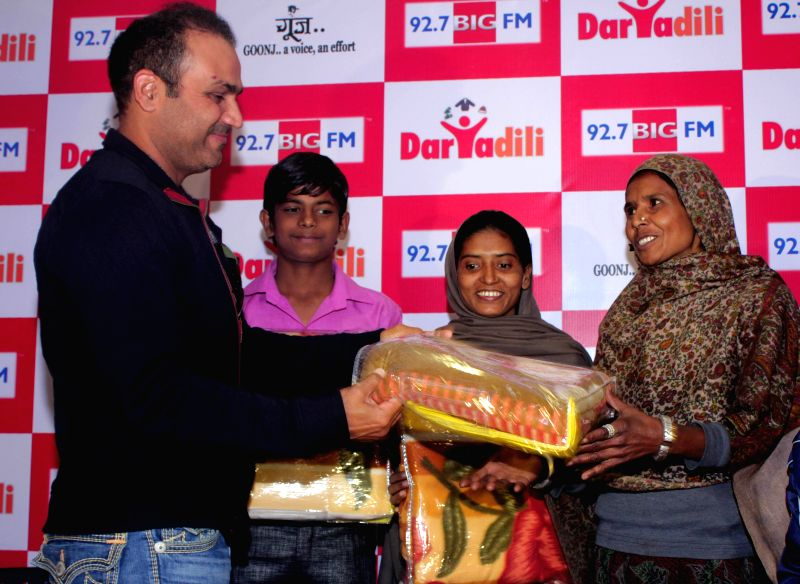Cricketer Virender Sehwag donates blankets to the poor during a philanthropic programme organised by 92.7 BIG FM and Goonj - NGO in New Delhi on Dec 12, 2014.