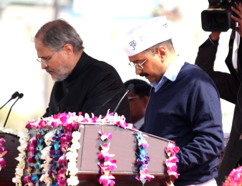 Delhi Lieutenant Governor Najeeb Jung administers oath to the Delhi Chief Minister Designate Arvind Kejriwal at Ramlila Maidan in New Delhi, on Feb 14, 2015. - Designate Arvind Kejriwal