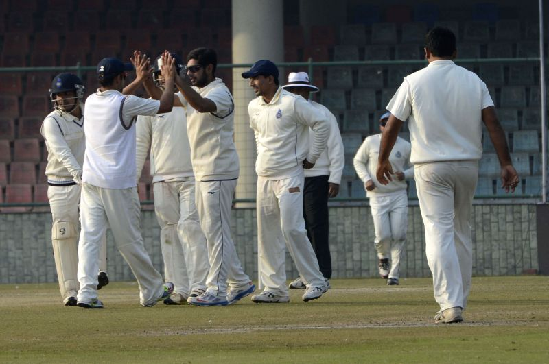 Delhi players celebrate fall of a wicket during a Ranji Trophy Match against Odisha in New Delhi, on Jan 15, 2015.
