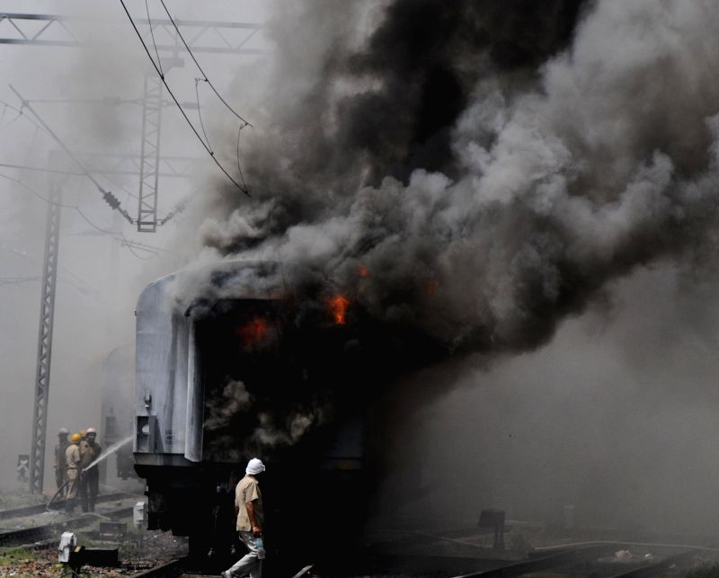 Firefighters douse the fire that broke out in a Bhubaneswar-New Delhi Rajdhani Express train at the New Delhi railway station yard, on April 21, 2015. At least five coaches of the train ...