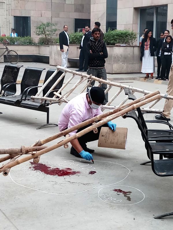 : New Delhi: Forensic experts collect samples from the spot where an undertrial Vinod alias Balle was shot dead when he was being taken back from the Rohini court in New Delhi on Nov 13, 2017. ...
