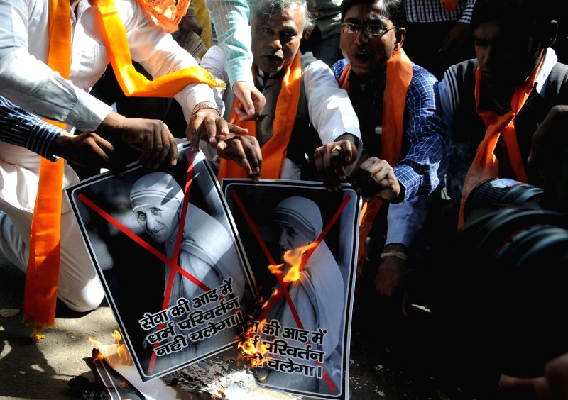 Hindu Sena activists burn posters of Mother Teresa at Jantar Mantar in New Delhi, on Feb 26, 2015.