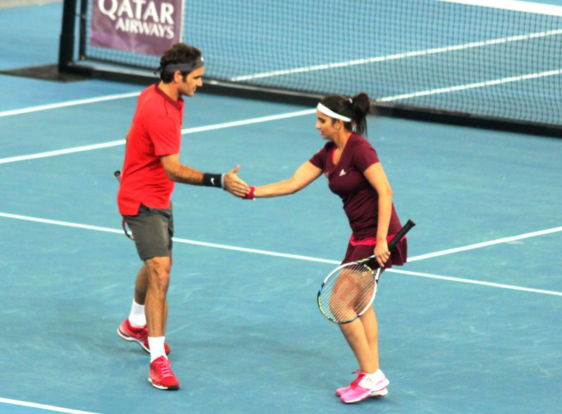 Indian Aces players Roger Federer and Sania Mirza during a match against Nenad Zimonjic and Kristina Mladenovic of UAE Royals during a mixed doubles IPTL match at Indira Gandhi Indoor ... - Sania Mirza