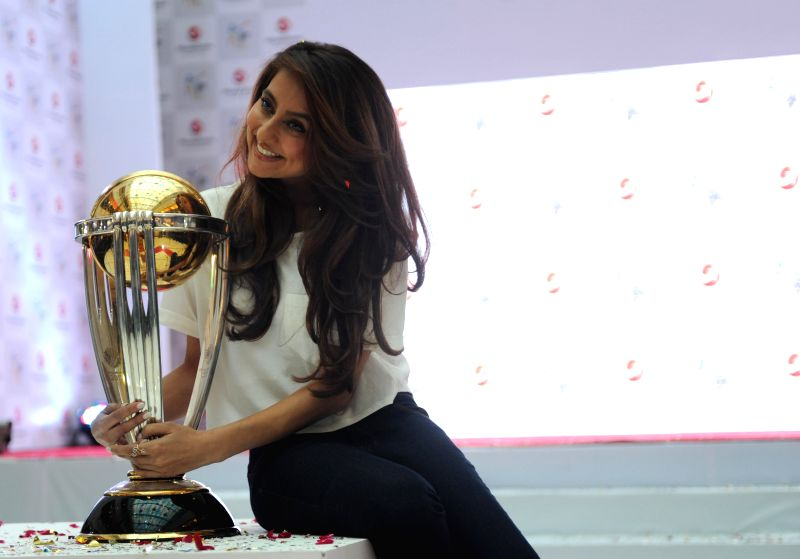Indian VJ, actress and singer Anusha Dandekar​ poses for a photo with the ICC World Cup 2014 trophy during a programme in New Delhi, on Dec 5, 2014.