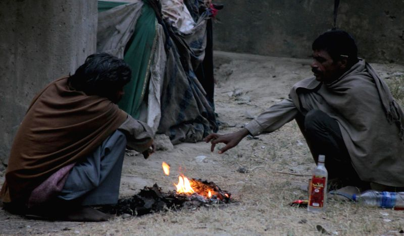 Men warm themselves around a fire with a bottle of liquor  in New Delhi, on Dec 14, 2014.