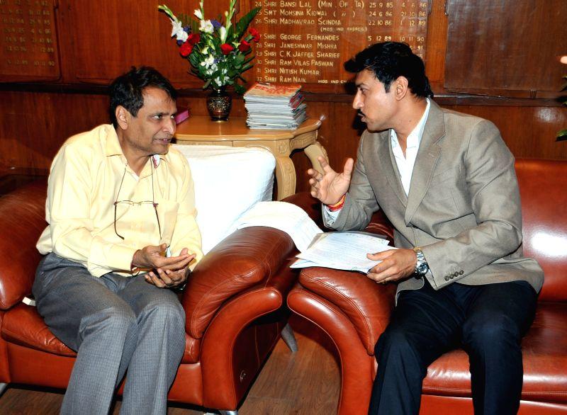 New Delhi: Union Minister for Railways Suresh Prabhakar Prabhu meets the Minister of State for Information and Broadcasting, Col. Rajyavardhan Singh Rathore, in New Delhi on April 9, 2015.