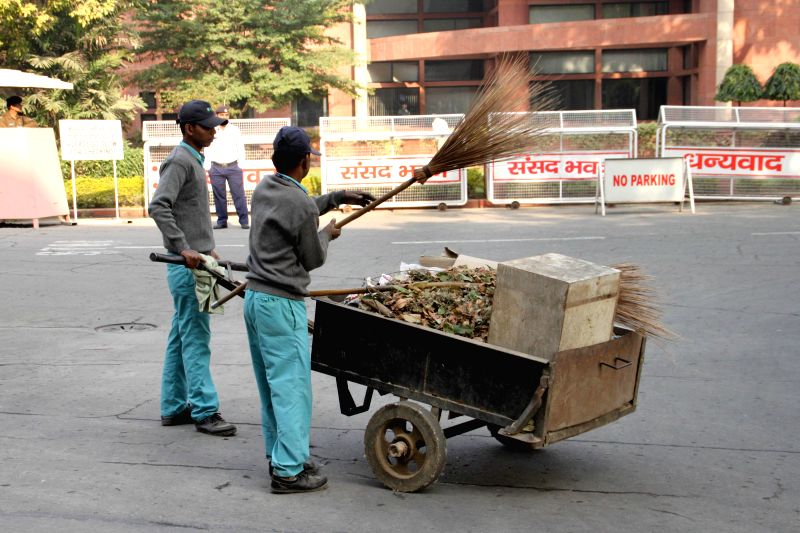 Parliament staff busy cleaning the Parliament premises on the first day of winter session in New Delhi, on Nov 24, 2014.