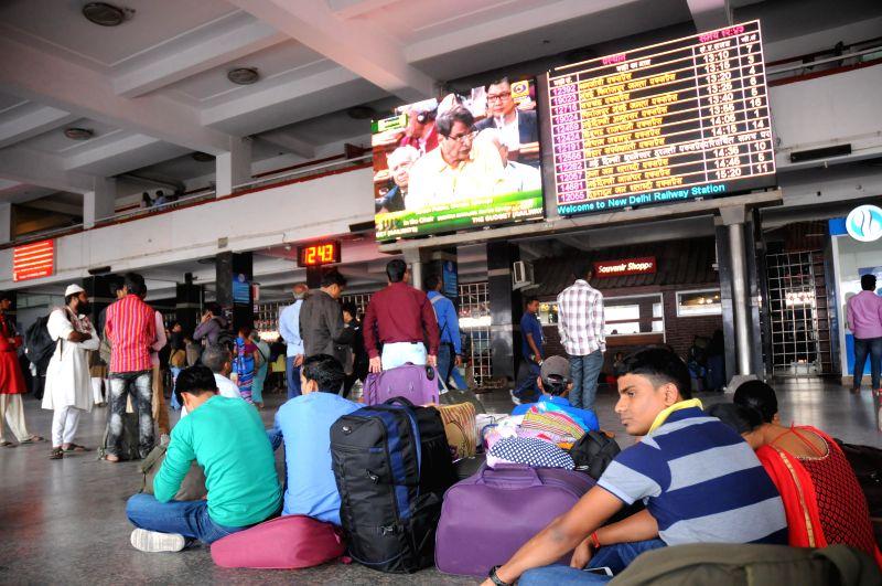 Passengers at New Delhi Railway station watch Union Railways Minister Suresh Prabhakar Prabhu present Railway Budget 2015-16 at the Parliament on a large screen, in New Delhi, on Feb 26, ... - Suresh Prabhakar Prabhu