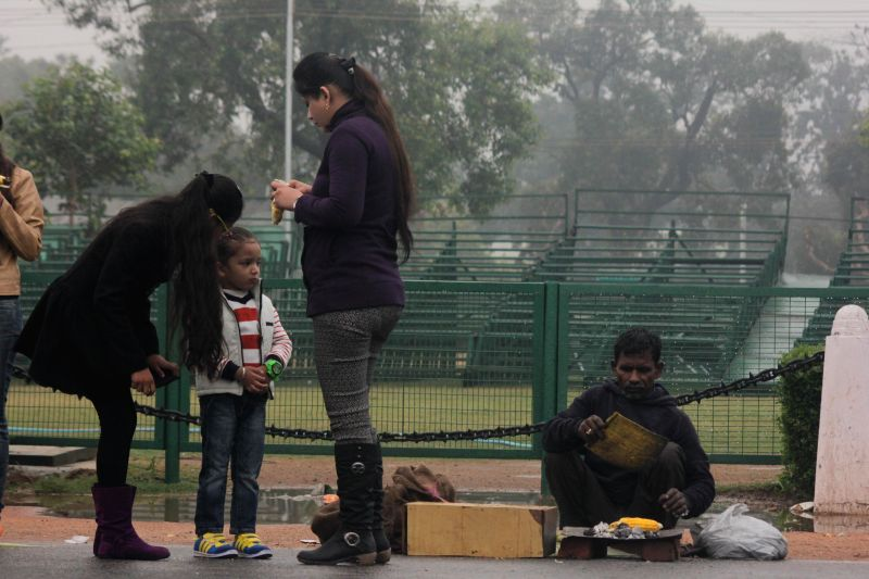 People enjoy roasted corns during winter rains in New Delhi on Dec 14, 2014.