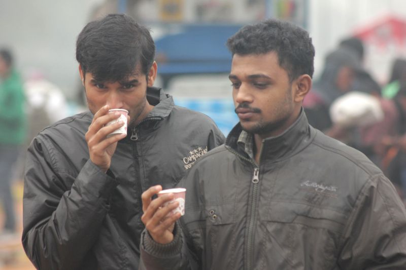 People enjoy tea on a foggy day at India gate in New Delhi, on Dec 14, 2014.