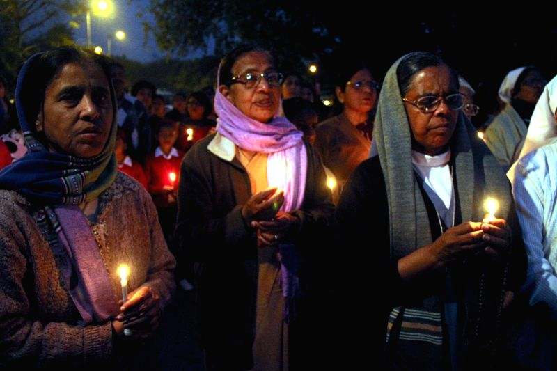 People hold a candlelight vigil against the recent gang rape of a nun in Ranaghat of West Bengal's Nadia district, in New Delhi, on March 16, 2015.