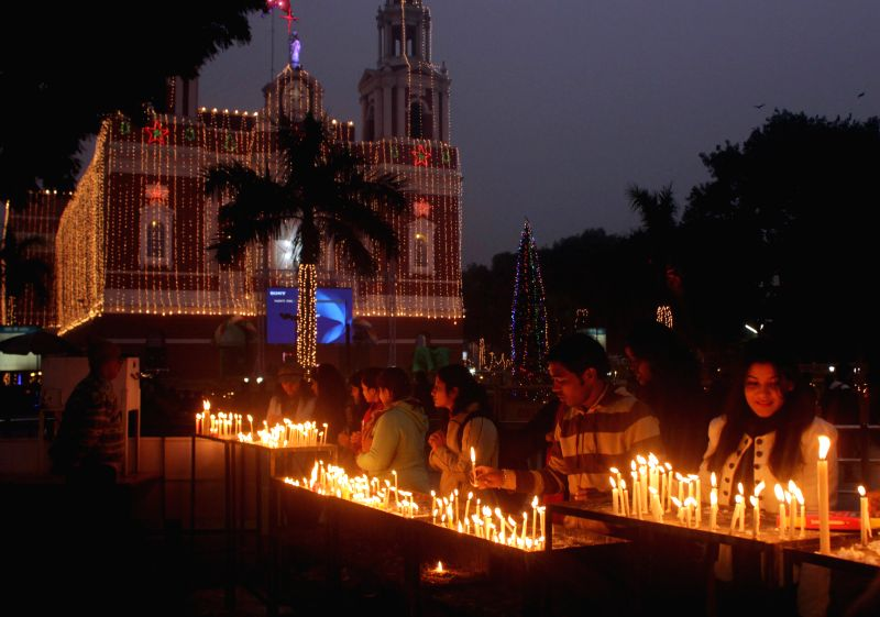 People light candles on the eve of Christmas at Gol Dak Khana Church in New Delhi on Dec 24, 2014.