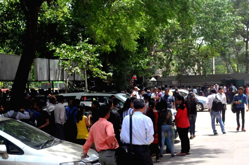 People rush out of their offices as earthquake jolts Delhi on April 25, 2015.