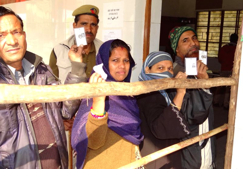 People show their voter's identity card as they queue-up to cast their votes at a polling booth during Delhi Assembly Polls in New Delhi, on Feb 7, 2015.