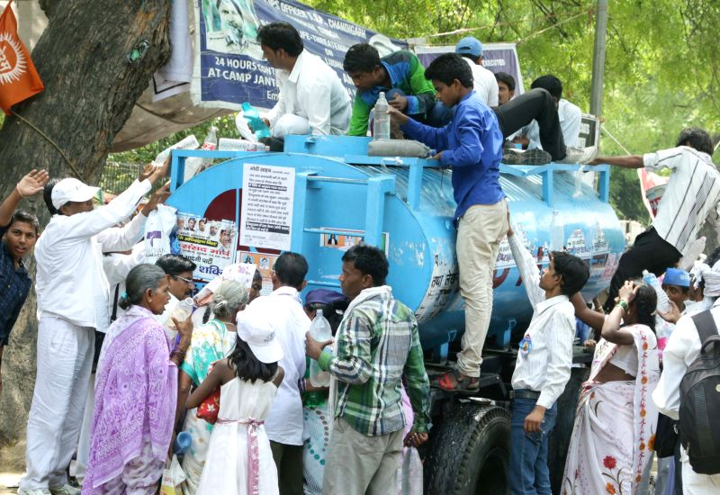 People struggle to fill up their bottles on a hot day at Jantar Mantar in New Delhi, on April 27, 2015.
