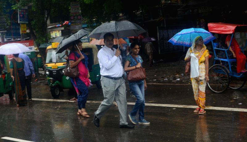 :New Delhi: People use umbrellas to shield themselves during rains, in New Delhi on July 26, 2018. (Photo: IANS).