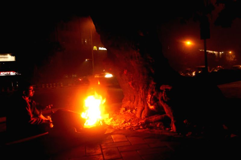 People warm themselves around a fire on a Delhi pavement.