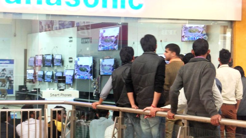 People watch an ICC World Cup 2015 match between India and Pakistan being played at the Adelaide Oval, outside an electronic showroom in New Delhi  on Feb 15, 2015.