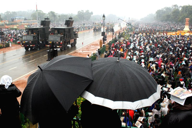 People witness the Republic Day parade 2015 with umbrellas at Rajpath in New Delhi, on Jan 26, 2015.