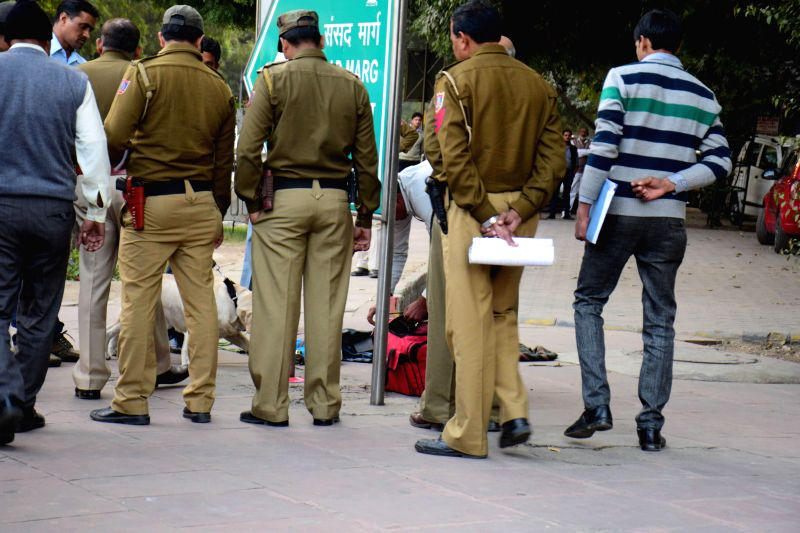 Policemen check an abandoned bag for explosives near Patel Chowk in New Delhi, on Dec 10, 2014.