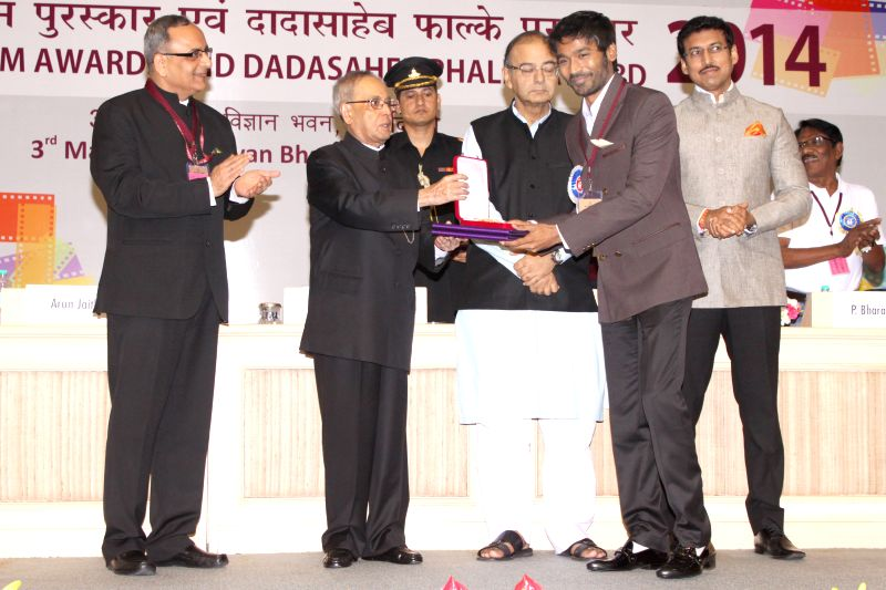President Pranab Mukherjee felicitates actor Dhanush at the 62nd National Film Awards ceremony organised at Vigyan Bhavan in New Delhi, on May 3, 2015. Also seen Union Minister for ... - Dhanush, Pranab Mukherjee, Arun Jaitley and Rajyavardhan Singh Rathore