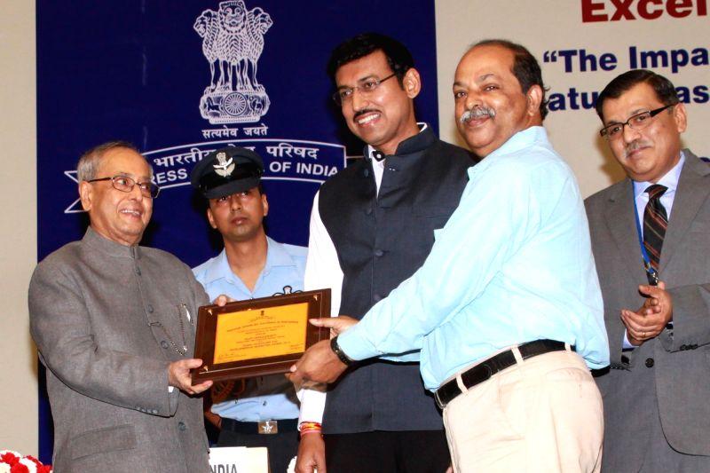 :New Delhi: President Pranab Mukherjee presents National Award for Excellence in Journalism 2015 to Sujit Chakraborty of IANS on during National Press Day at Vigyan Bhavan in New Delhi, on Nov 16, ... - Pranab Mukherjee