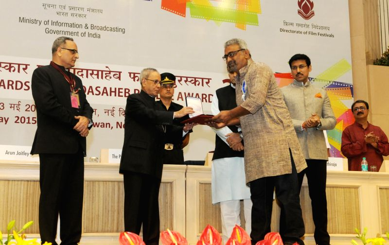 "President Pranab Mukherjee presents the Rajat Kamal Award for Best Biographical Film: ""Aamaar Katha: Story of Binodini"" in Non Feature Films Section to the Director, Tuhinabha Majumdar ... - Pranab Mukherjee"