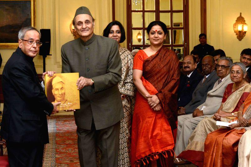 President Pranab Mukherjee receives the first copy of 'Remembering Baba - Dr. Rajendra Prasad' - a Coffee Table Book, from Congress leader Karan Singh at Rashtrapati Bhavan in New Delhi, .. - Pranab Mukherjee and Karan Singh