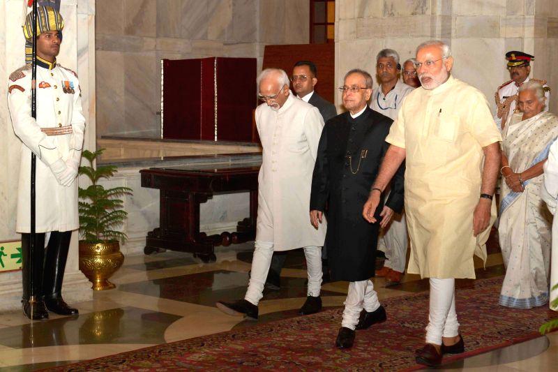 President Pranab Mukherjee, Vice President Mohd. Hamid Ansari and Prime Minister Narendra Modi at the Defence Investiture Ceremony– II, at Rashtrapati Bhavan, in New Delhi on April 26, ... - Narendra Modi and Pranab Mukherjee